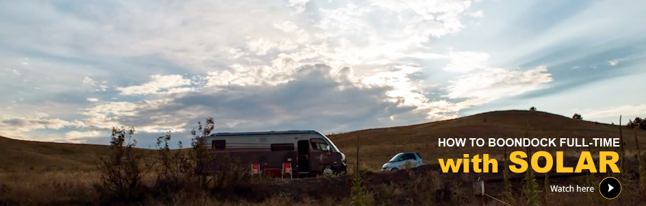"A large RV and smart car in the middle of a field, ""How to boondock full-time with Solar"""